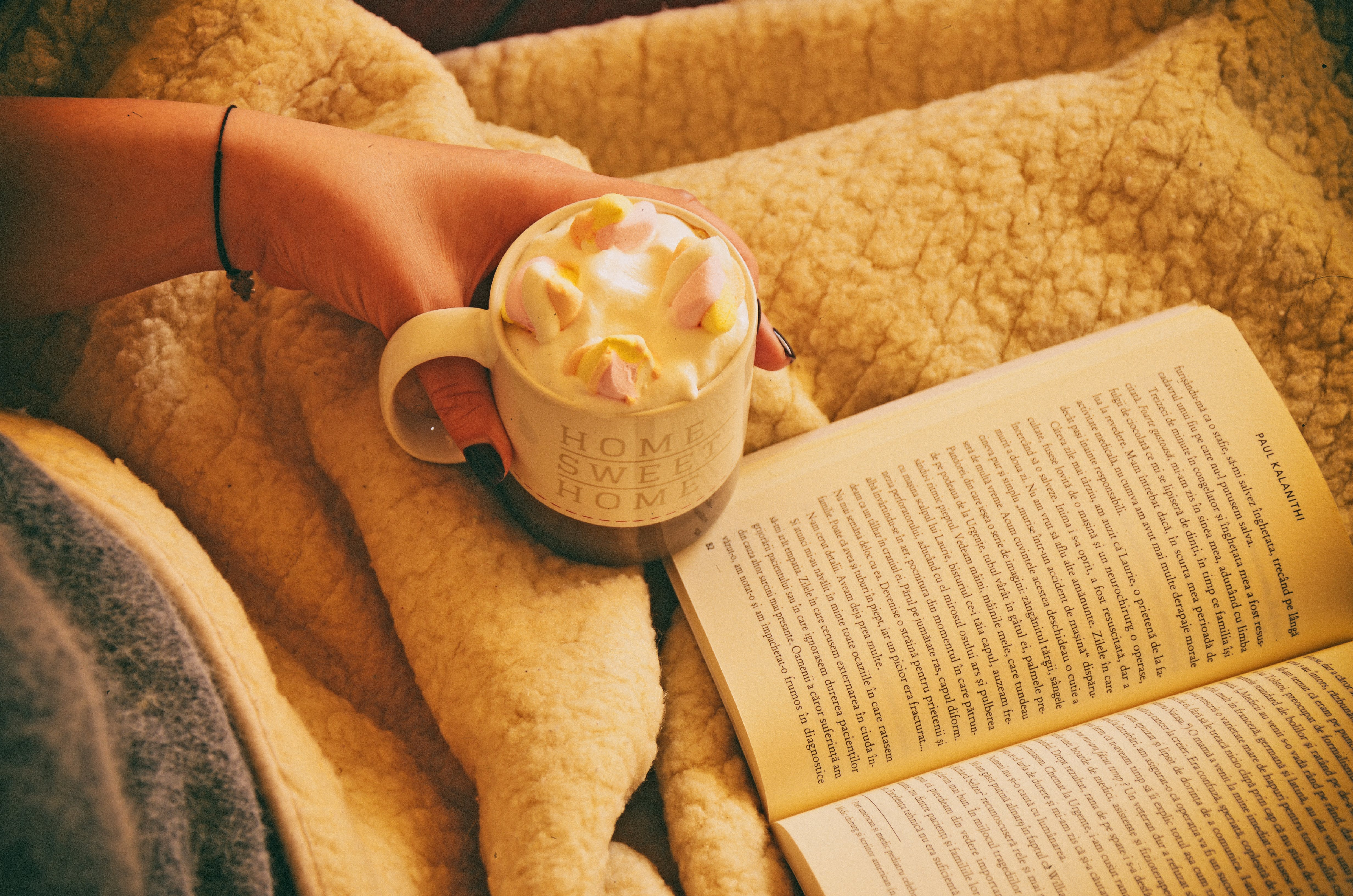 Person Holding Mug Filled With Pastry Beside Open-book