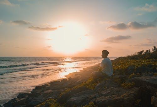 水域の近くの岩の上に座っている男