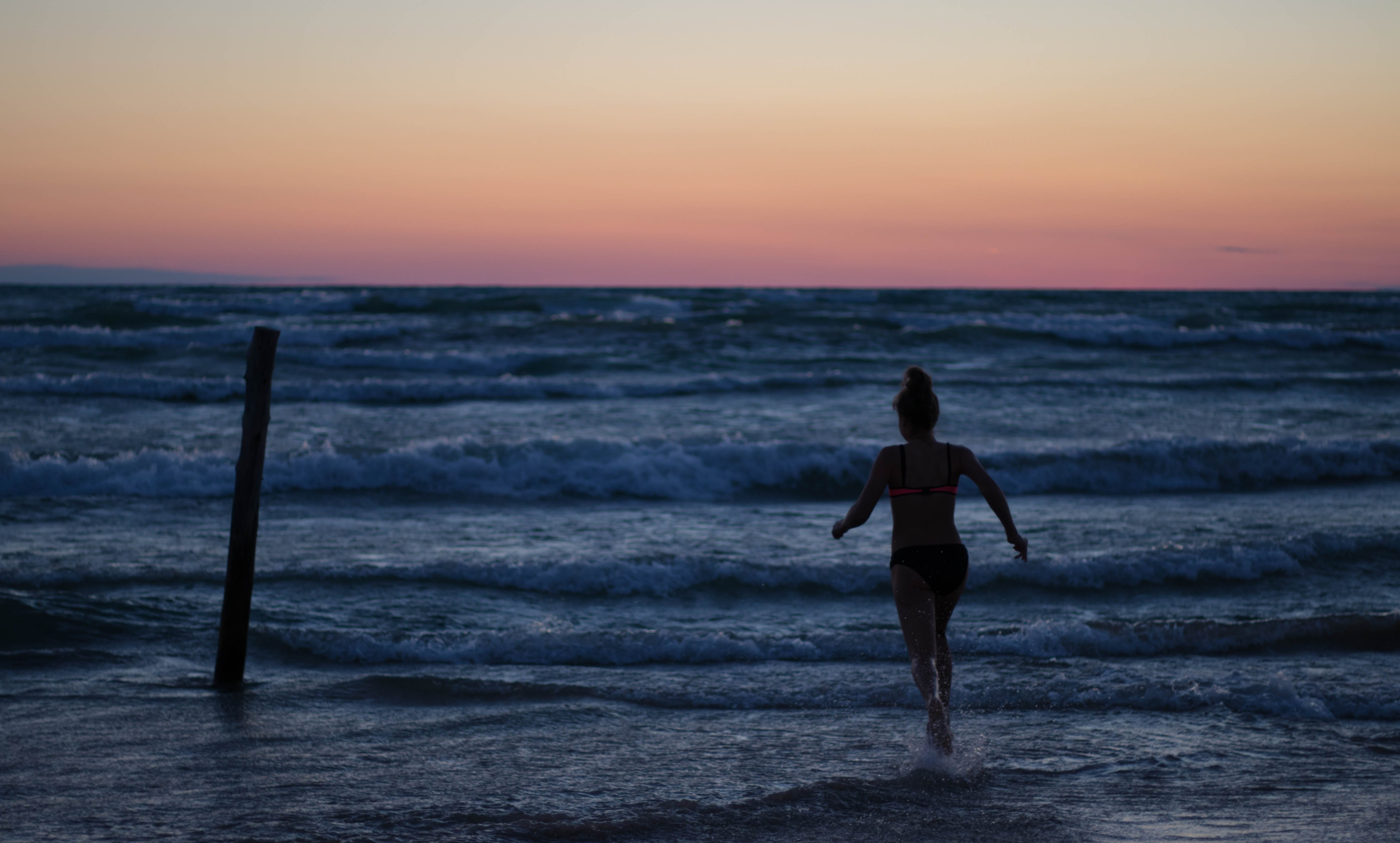 Woman Running Towards Body of Water