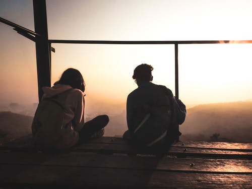 Two Persons Sitting by the Deck Facing Sunrise