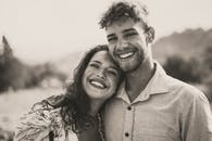 Grayscale Photo of Woman Leaning Head on Man's Right Shoulder