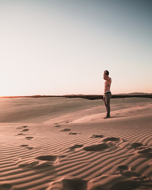 Photo of Topless Man Standing on Desert