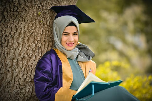 Woman Wearing Academic Dress Leaning on Tree