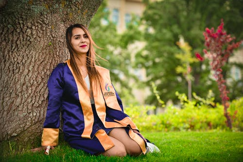 Woman Wearing Blue and Orange Academic Dress Sitting on Green Grass Field