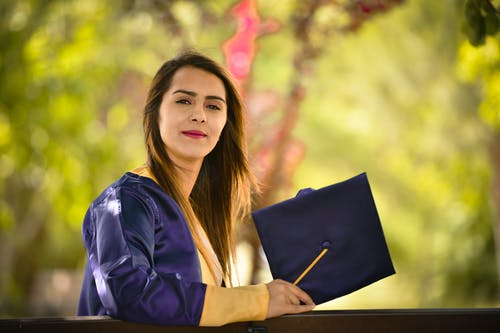 Woman Standing While Wearing Blue Academic Gown
