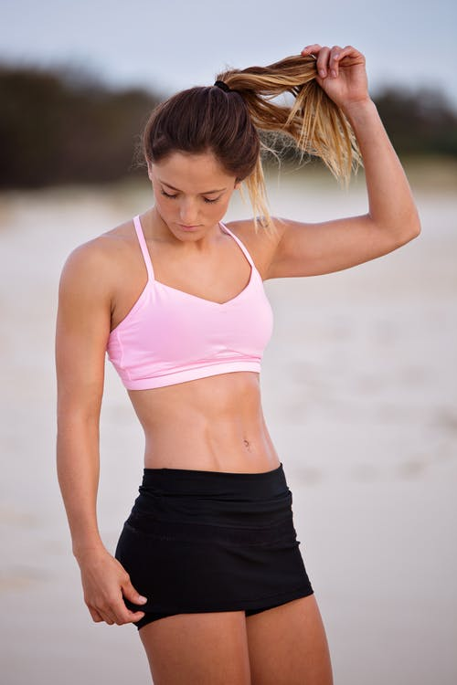 Woman Touching Her Ponytail And Wearing Pink Sports Bra