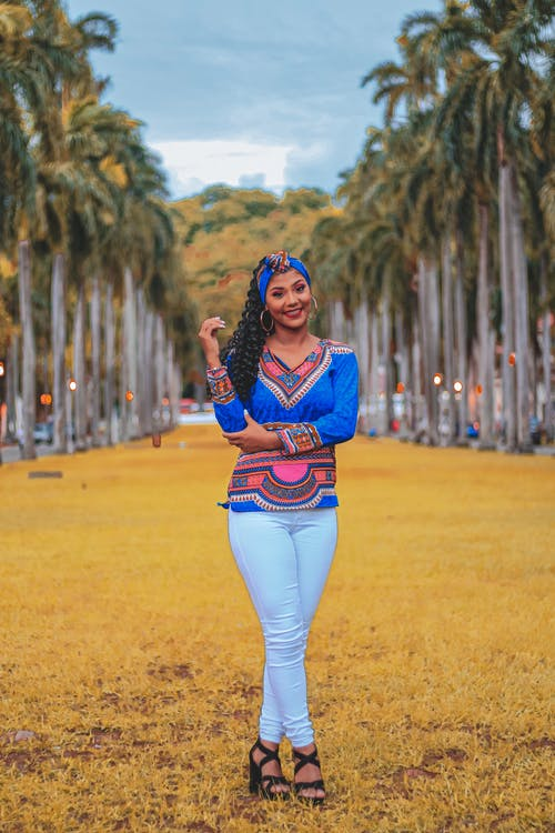 Photo of Smiling Woman in Blue Dashiki and White Jeans Standing on Yellow Grass Near Palm Trees Posing