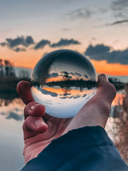 Clear Glass Ball With Reflection Of Body Of Water During Golden Hour
