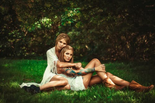 Photo of Two Women Sitting on Grass