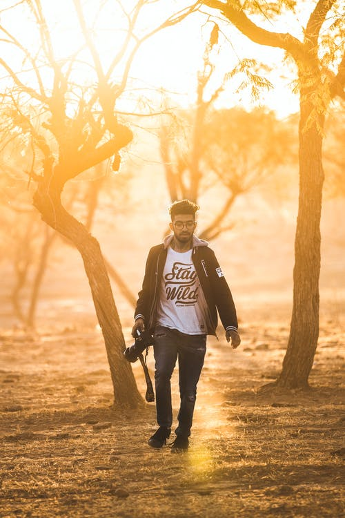 Photo of Man Holding Digital Camera While Walking