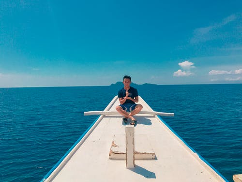 Man Doing Lotus Position on Boat