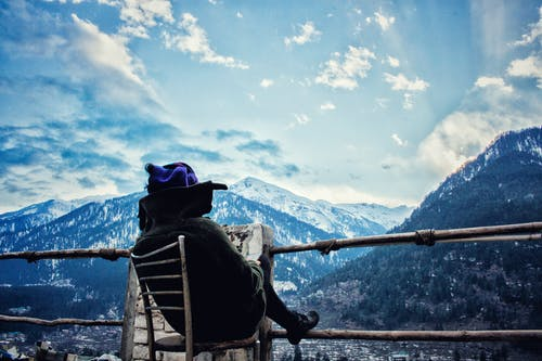 Person Sitting White Chair While Reading in Front-of Mountain Scenery