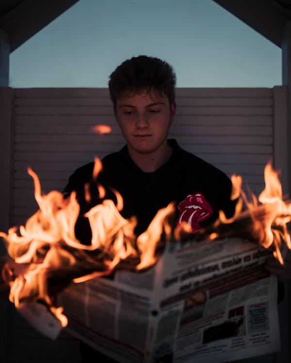 Man Wearing Black Shirt Reading Burning Newspaper