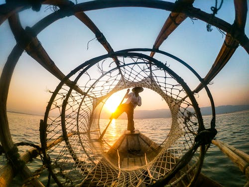 Man Standing On Boat During Sunrise