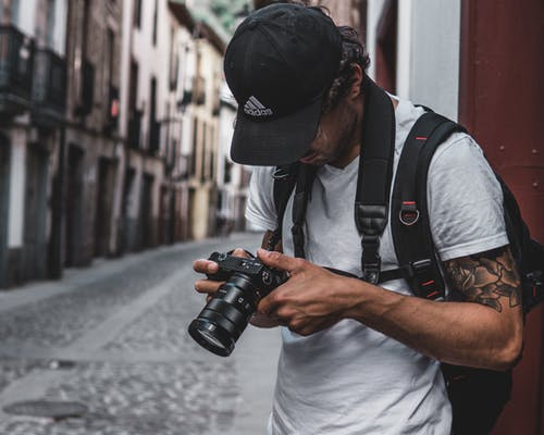 Photo of Man Standing in Alley Holding Dslr Camera Looking at Photos