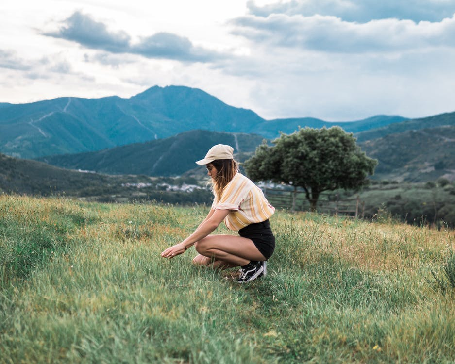 Side View Photo of Woman Kneeling on Grass Field With Mountains in the Background