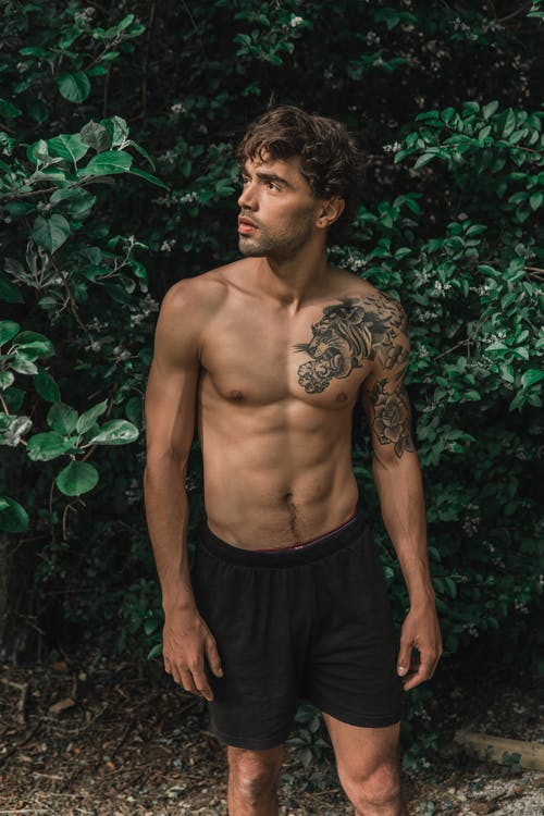 Photo of Shirtless Man in Black Board Shorts Standing In Front of Green-leafed Plants Looking Away