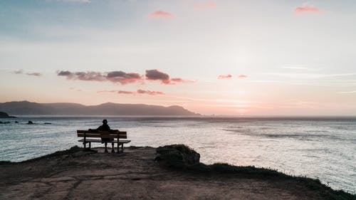 Person Sitting on Bench Facing the Sea