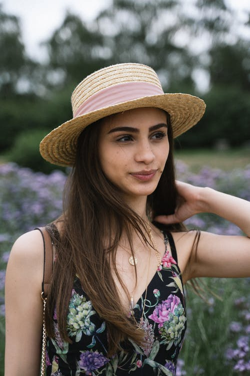 Selective Focus Portrait Photo of Woman in Sun Hat and Floral Dress Standing in Flower Field