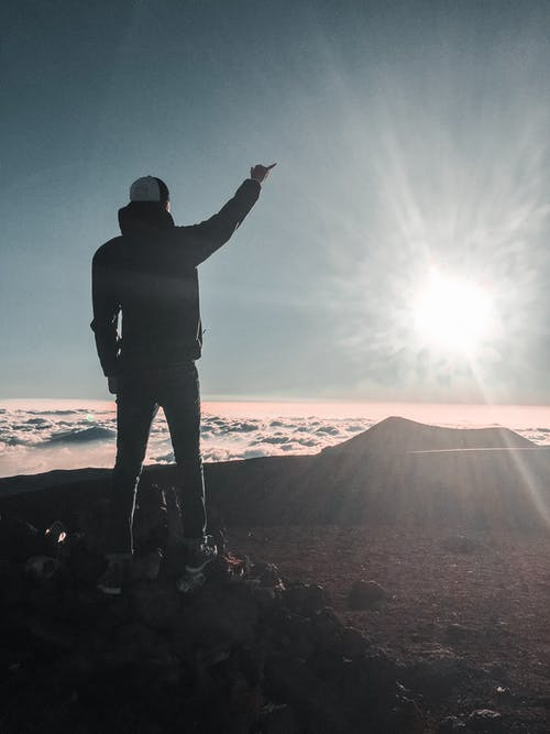 Man Standing Near Sea of Clouds