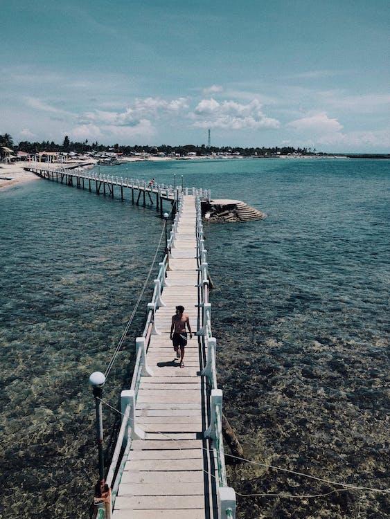 Man Walking on Brown Beach Dock