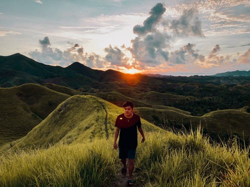 Man Walking in Ridge of Grass Covered Hill at Sunset