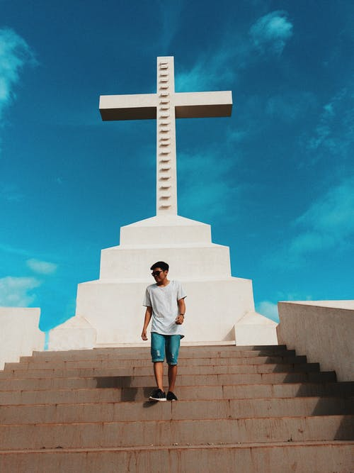 Man Standing on Stair Under Cross Statue Background