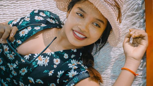 Close-up Photo of Smiling Woman in Black Floral Top and Sun Hat Holding Sunglasses Lying on White Hammock Looking Away