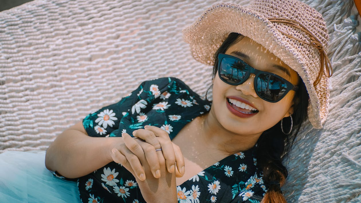 Close-up Photo of Smiling Woman in Black Floral Top, Sun Hat, and Sunglasses Lying on White Hammock