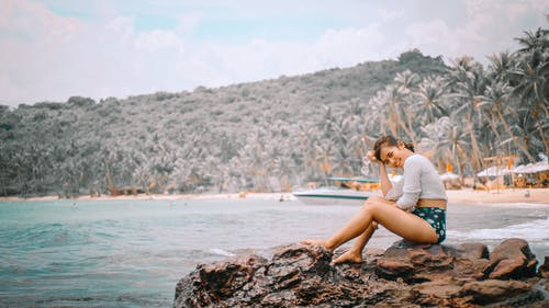 Photo of Smiling Woman Sitting on Rocks Near Beach