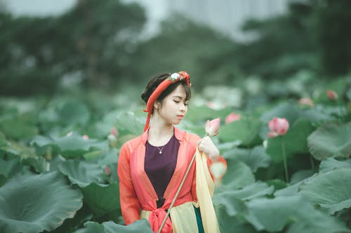 Selective Focus Photo of Woman in Colorful Outfit with Her Eyes Closed Holding Pink Flower Standing in the Middle of Flower Field