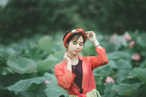 Selective Focus Photo of Woman in Colorful Outfit Posing with Her Eyes Closed Standing in the Middle of Flower Field