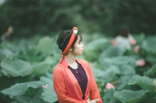 Selective Focus Side View Photo of Woman in Colorful Outfit Posing with Her Eyes Closed Standing in the Middle of Flower Field
