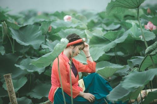 Woman Sitting Near Plants