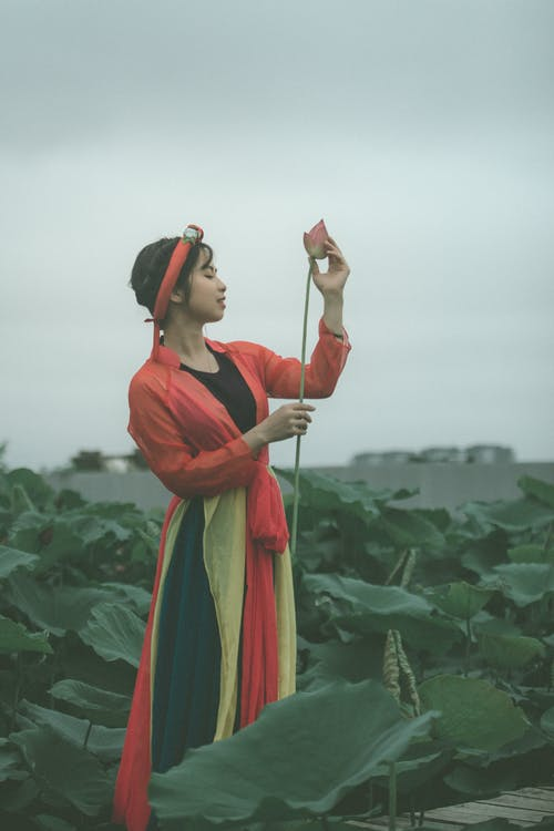 Side View Photo of Woman in Colorful Outfit Holding Pink Flower Posing with Her Eyes Closed Standing in the Middle of Flower Field