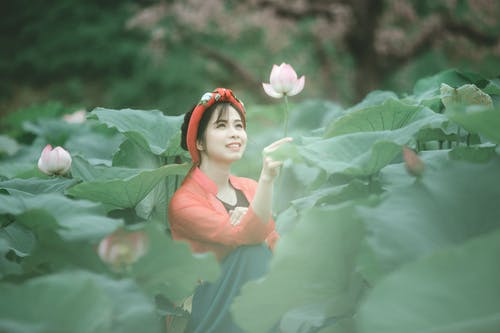 Photo of Smiling Woman Holding a Pink Flower While Sitting in the Middle of a Flower Field