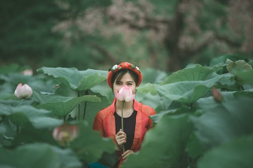 Woman in Red Jacket Holding Pink Flower