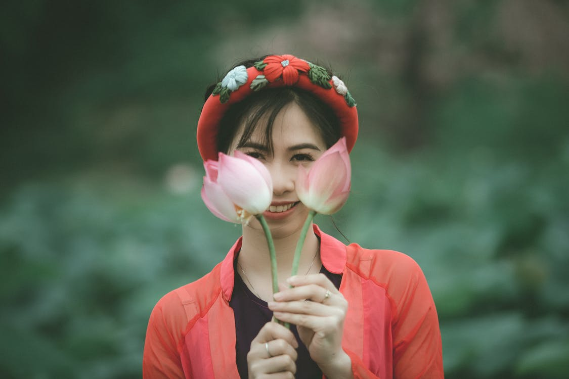 Selective Focus Photo of Smiling Woman Holding Up Pink-Lotus Flowers In Front Of Her Face