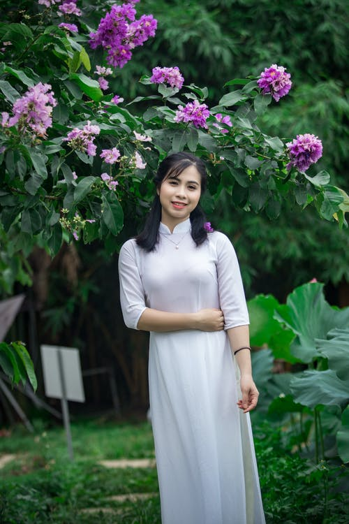 Photo of Smiling Woman in White Dress Standing Under Purple Flowers
