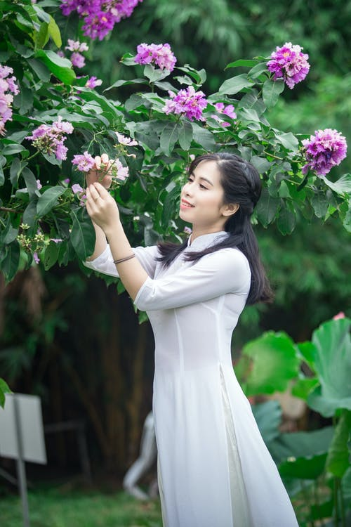 Side View Photo of Smiling Woman in White Dress Picking Purple-petaled Flowers
