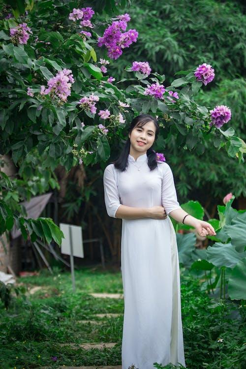 Smiling Woman Standing Under Purple Flowering Plant