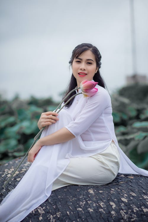 Selective Focus Photo of Woman in White Sheer Top Holding a Pink Lotus Flower