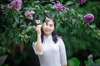 Portrait Photo of Smiling Woman in White Dress Standing Under Purple Flowers
