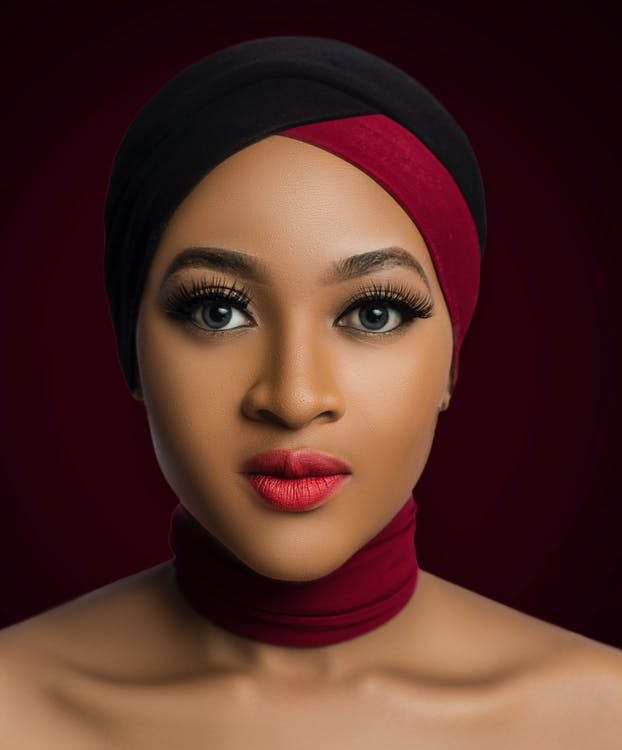 Portrait Photo of Topless Woman in Maroon and Black Headscarf and Maroon Fabric Choker