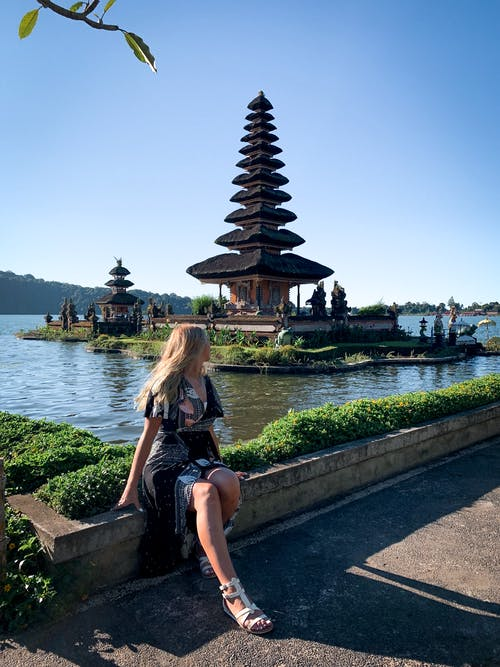 Photo of Woman Sitting Near Plants Looking at Pagoda