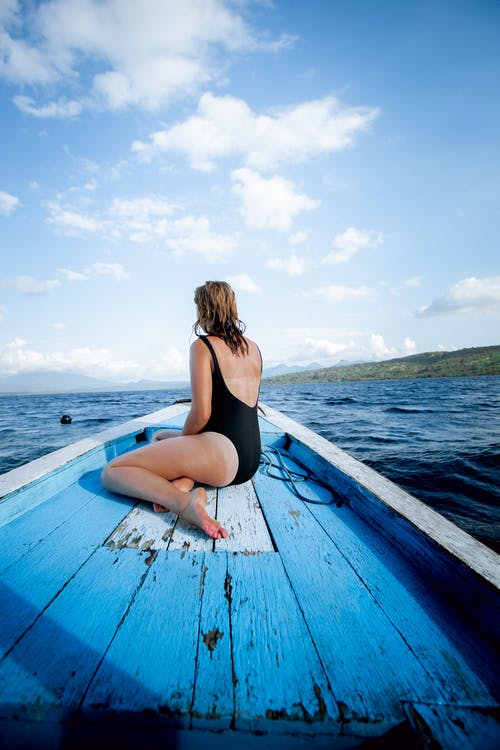 Photo of Woman Sitting on Wooden Boat