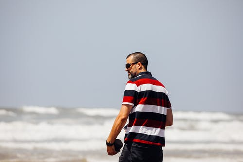 Man In Striped Shirt Near Body Of Water