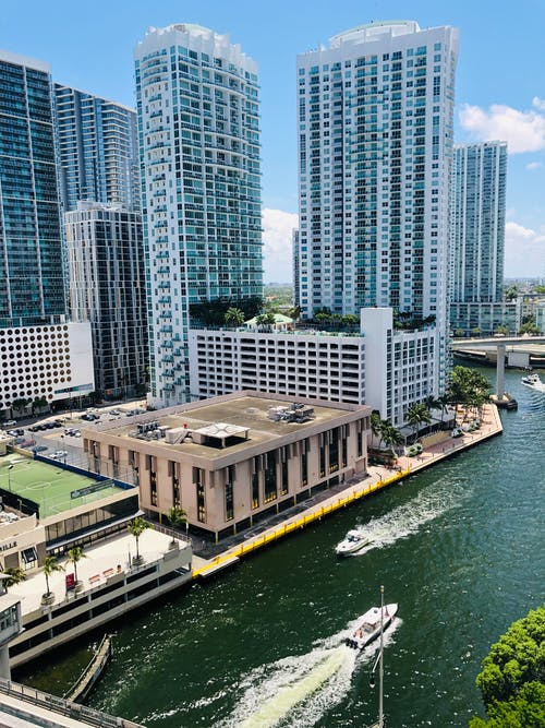 Photo of Motorboats on River Near Buildings