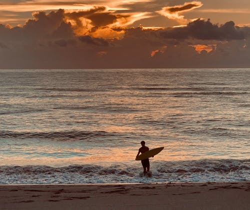 Photo of Man Carrying Surfboard on Seashore During Golden Hour