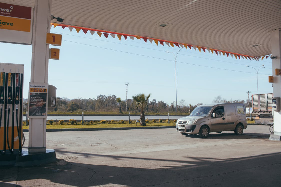 Car near gas station against cloudless sky